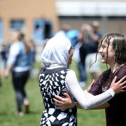 Students embrace after running through a water cannon to celebrate the last day of school at Crestview Elementary in Holladay on Friday, May 27, 2016.