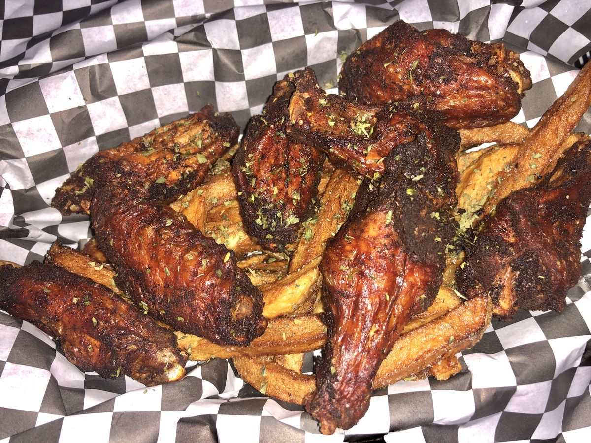 Wings with fries in a checkered wrapped basket.