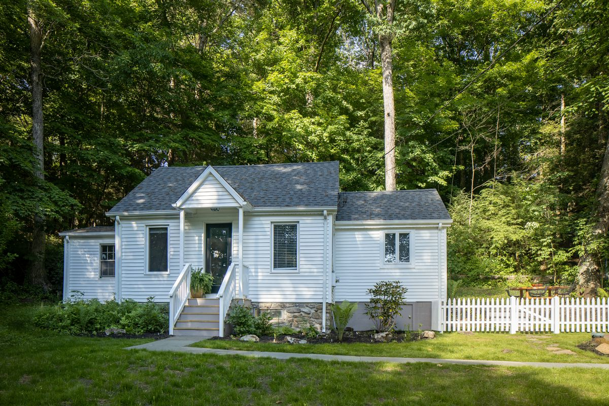A small Cape Cod style white cottage sits on green grass with trees behind it.