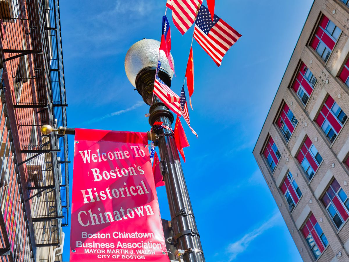 """Looking up at a street lamp between two buildings, and there are little American flags and a sign reading """"Welcome to Boston's Historical Chinatown"""" hanging off it."""