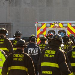 Chicago Fire Fighters and Police Officers walk into the loading area of the Cook County Medical Examiners Office to give a final salute to a off duty Chicago Police Officer who was fatally shot inside his car in the River North neighborhood, Saturday, March 23, 2019, in Chicago.   Tyler LaRiviere/Sun-Times