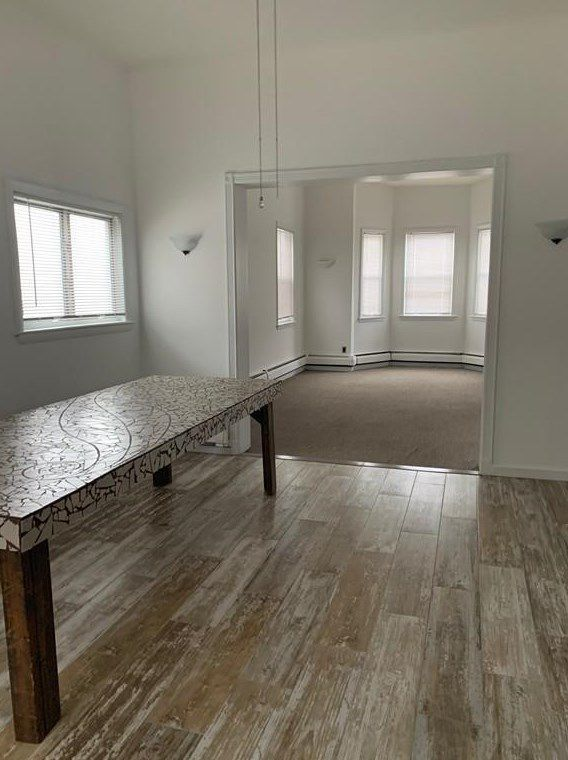 The view of a kitchen with hardwood floors out into a living room, and over the kitchen's long table.