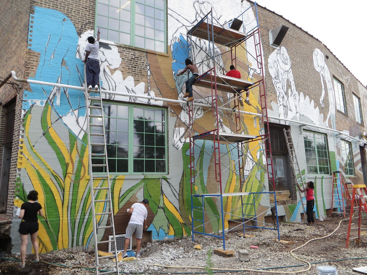Volunteers worked with artist Joe Miller to produce the mural at The Plant.