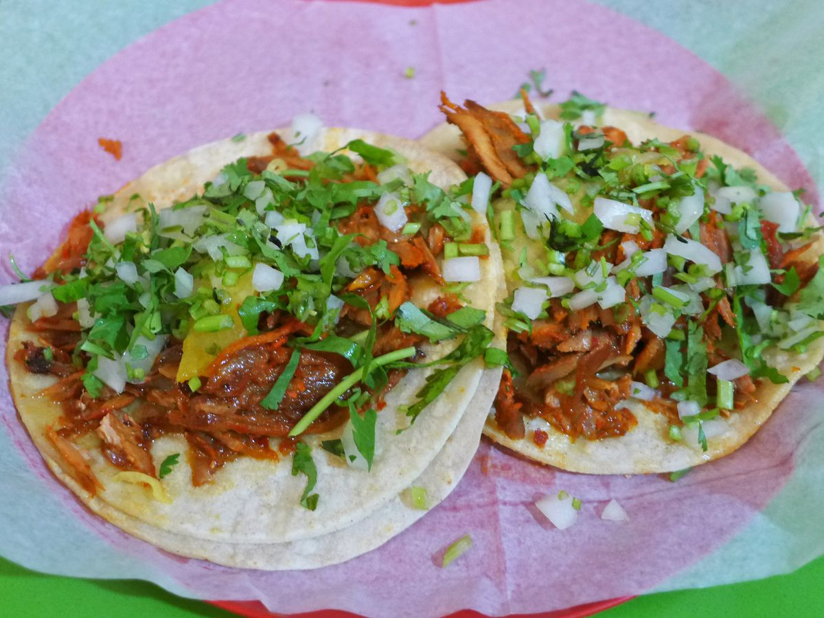 Two tacos spread flat with meat, onions, cilantro, and red salsa.