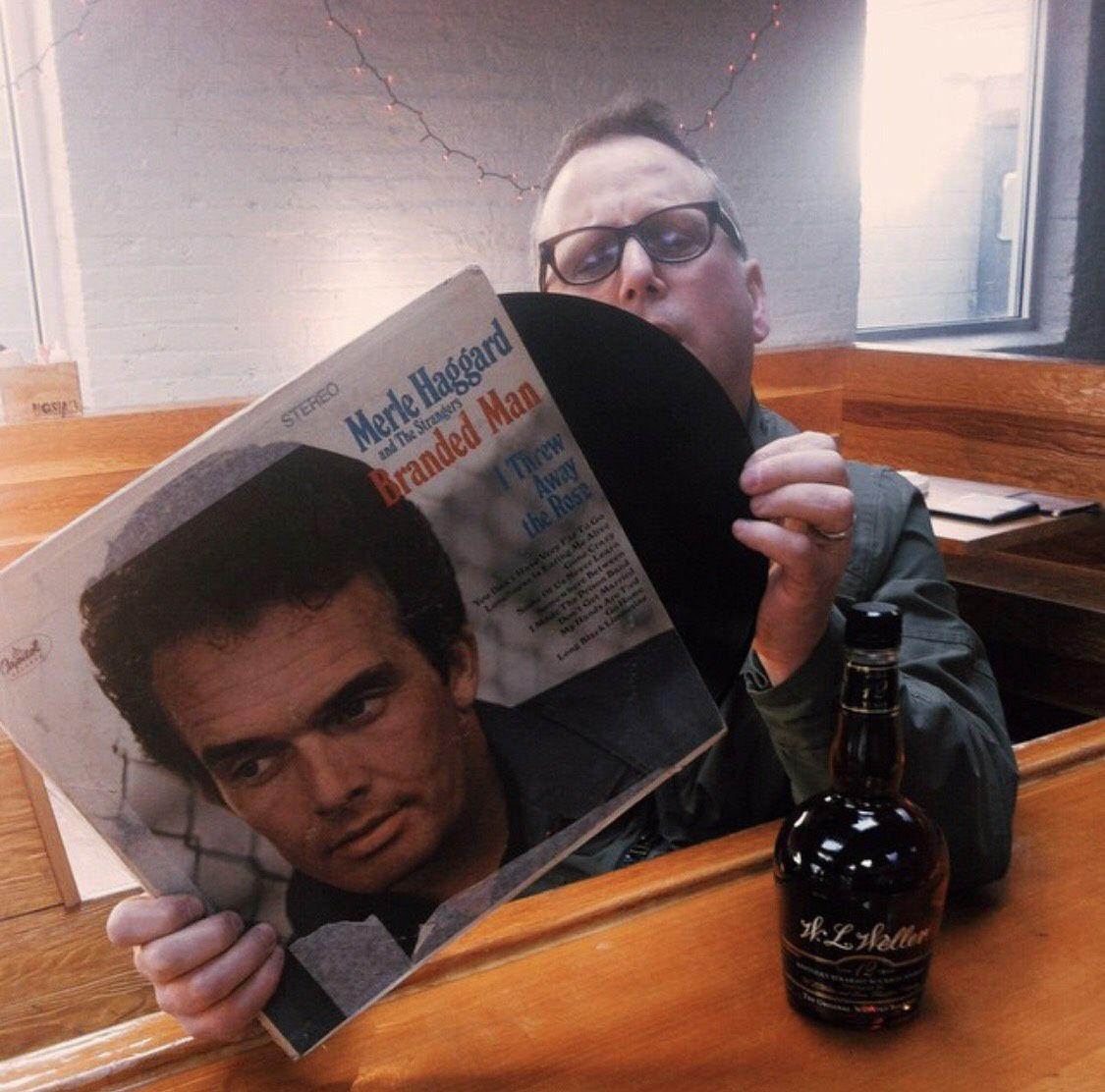 Paul Kahan sits at the bar at Big Star while looking at and pulling a record out of a Merle Haggard sleeve.