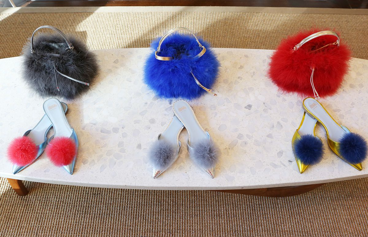 Three pairs of pointy-toed shoes with big pom-poms on the toe, in blue, silver, and yellow.