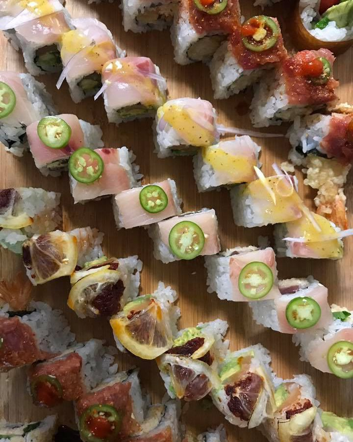 Rolls of sushi arrayed in diagonal lines with various toppings