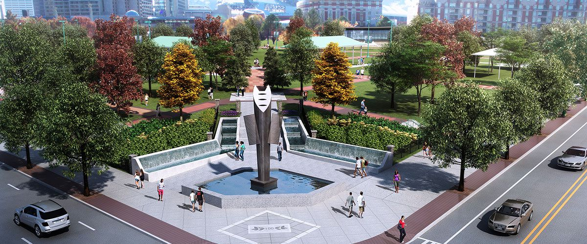 An aerial view of a park with a fountain, trees, and a lawn. There are people walking in the plaza that surrounds the fountain.