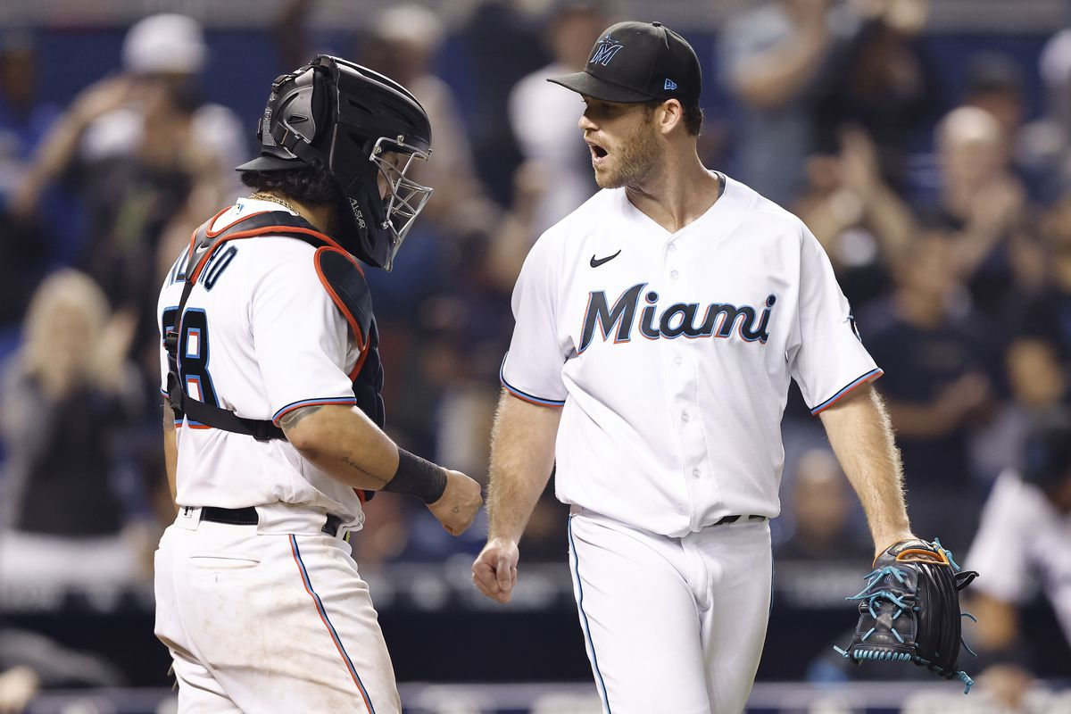 Anthony Bender #80 and Jorge Alfaro #38 of the Miami Marlins celebrate the final out as they defeat the Los Angeles Dodgers 5-4 at loanDepot park