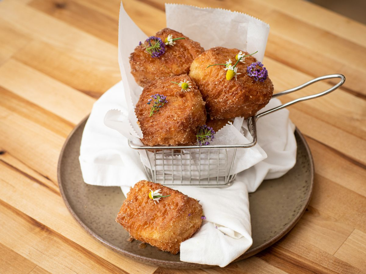 Golden brown cubes of fried dough set in a wire basket with a white cloth on a brown circular plate set on a light wooden table