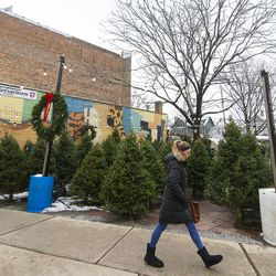 A woman walks by a pop up Christmas Tree seller on Lincoln Avenue, in Lincoln Square. | Tyler LaRiviere/Sun-Times