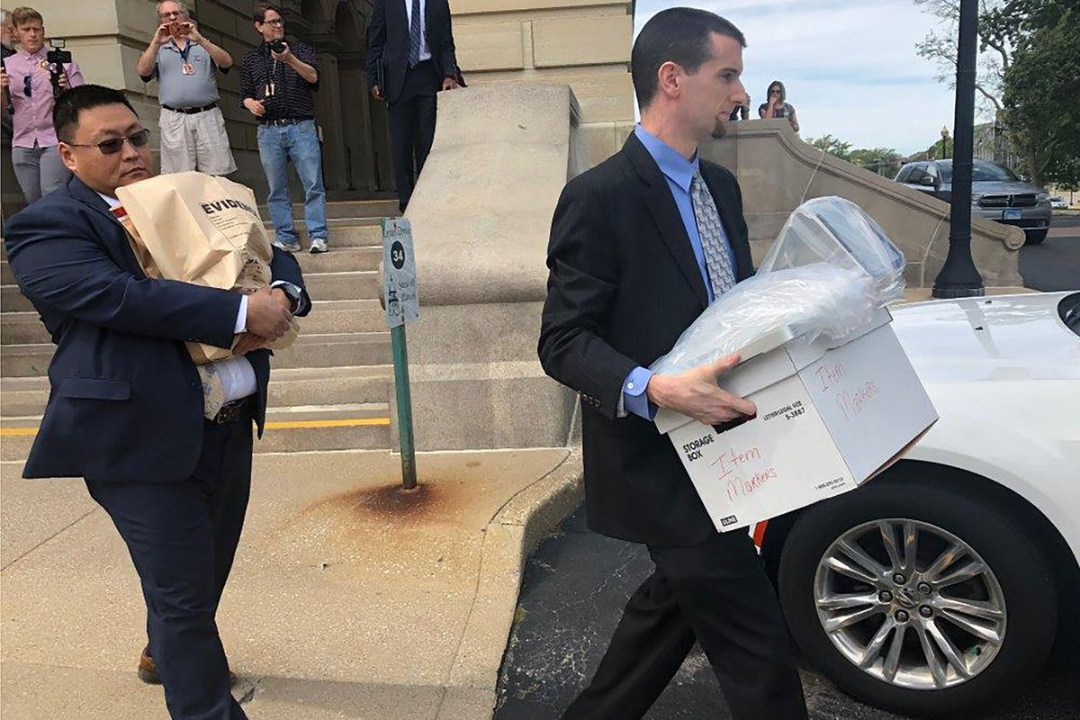 FBI agents carrying boxes and a bag marked EVIDENCE leave the state Capitol in Springfield after raiding the office of state Sen. Martin Sandoval.