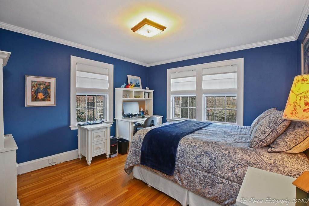 A corner bedroom with a bed and two windows facing each other.