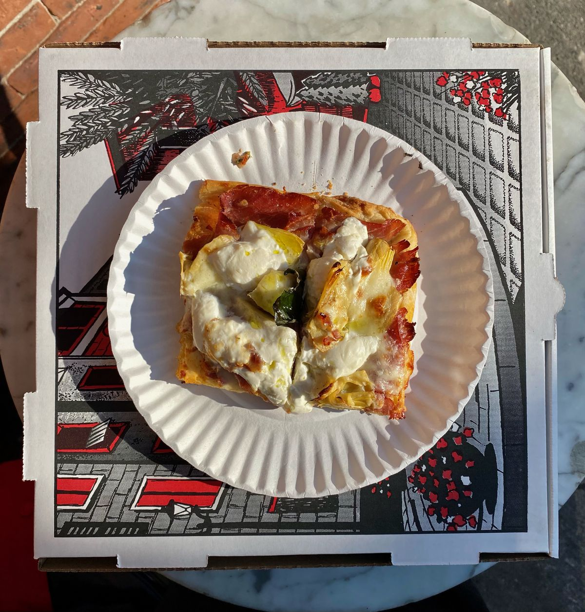 An overhead photograph of a slice of pizza on a plate, perched on a pizza box outdoors