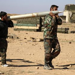 """FILE - In this Feb. 17, 2016 file photo, soldiers from the Syrian army carry a rocket as they prepare to fire at Islamic State group positions in the province of Raqqa, Syria. A major battle to liberate the northern Syrian city of Raqqa from Islamic State militants is looming, with U.S. officials looking to build on momentum from the battlefields in Mosul. Armed with a new Pentagon plan to """"rapidly defeat"""" the militants in both countries, President Donald Trump is now mulling options for upping the fight, which a top U.S. commander says he expects to be concluded within six months ."""