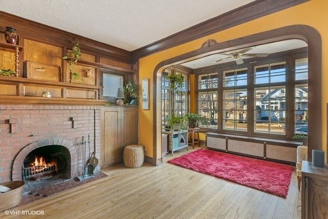 An original fireplace with a full wall wooden built in shelving and a front sun room.