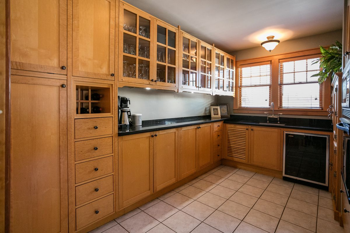 Butler's pantry with a row of cabinets, some glass, some wood, and black granite counters.