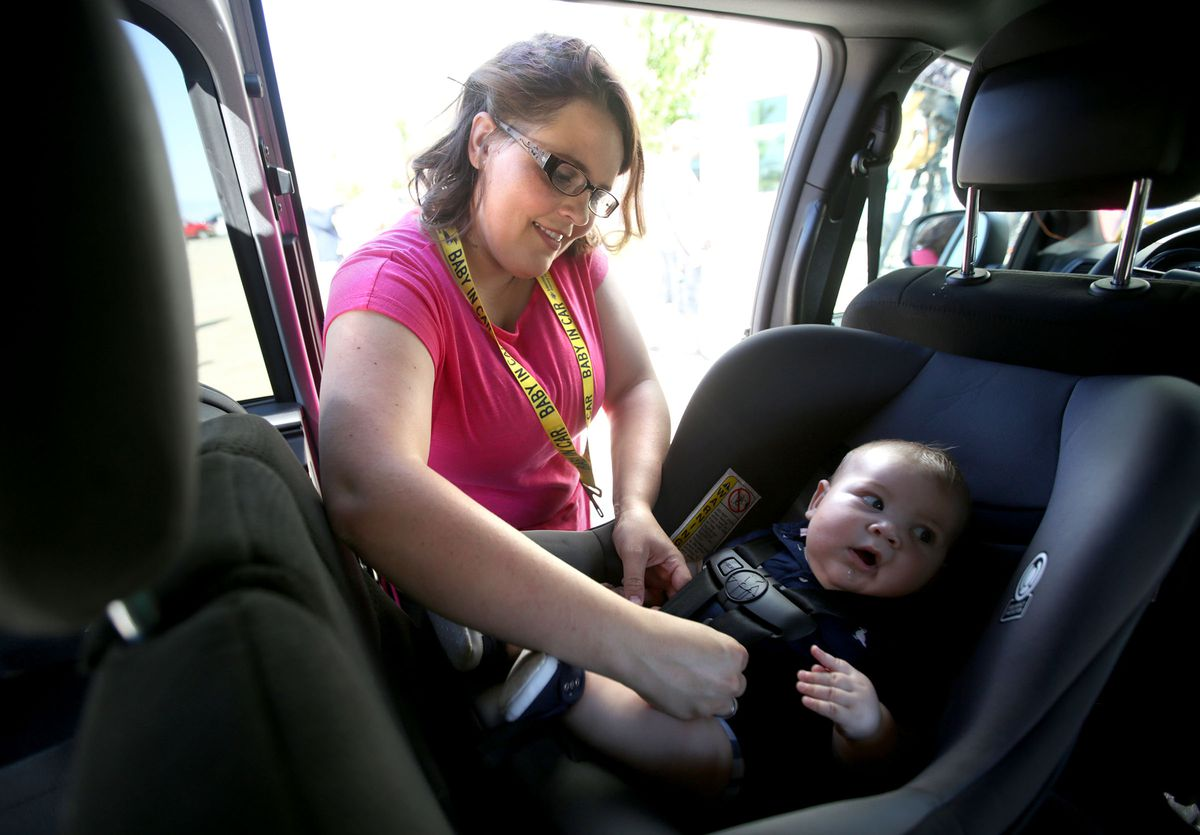 Felicia Ellis demonstrates how to use Baby Safety Snaps, a safety device that helps prevent heat-related child injuries and deaths inside vehicles, with her baby, Sawyer, outside the Primary Children's Hospital Outpatient Services Building in Salt Lake City on July 10, 2018.
