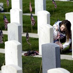 Athena Zaharias, 13, of West Jordan puts out American flags in the veterans section of the Salt Lake City Cemetery on Saturday, May 26, 2012.  Zaharias, her brother, and her grandfather, Dan Zaharias, Vietnam War veteran and Commander of VFW Post 409, and other helpers stake more than 2,000 flags in the cemetery.