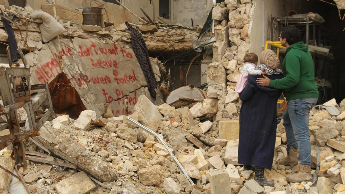 "A scene from the documentary ""For Sama"" in which a man, woman, and child stand looking at the bombed remains of a building where someone has spray painted, ""We don't want to leave, we were forced to flee."""
