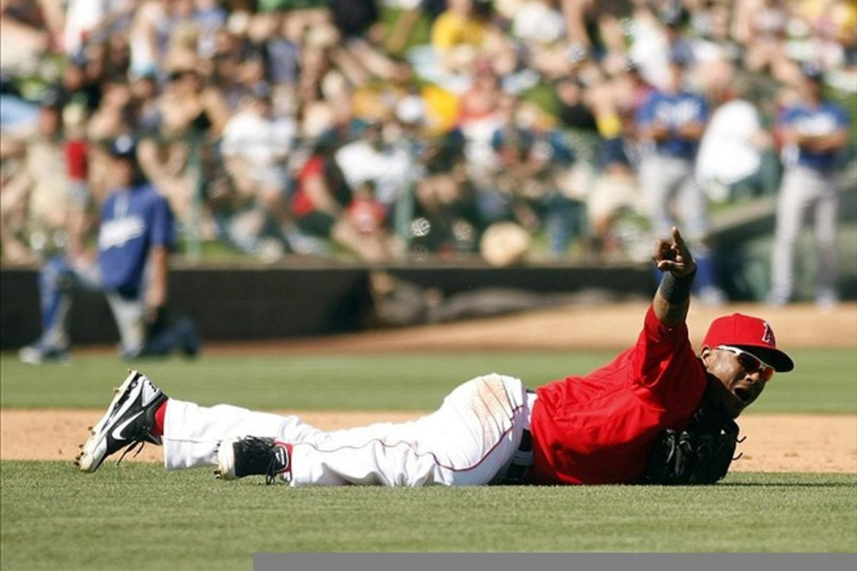 March 12, 2012; Tempe, AZ, USA; Los Angeles Angels shortstop Erick Aybar (2) points to first base after knocking the ball down against the Los Angeles Dodgers in the fourth inning at Tempe Diablo Stadium.  Mandatory Credit: Rick Scuteri-US PRESSWIRE