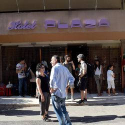 Greek activists and refugees mingle in front of City Hotel Plaza in Athens, Greece, in July 2016. The abandoned hotel has been occupied by Greek activists and turned into a refugee camp.