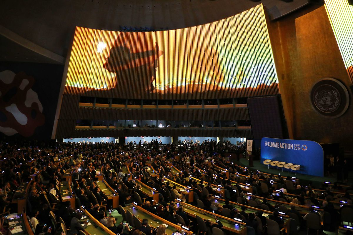 The General Assembly Hall during the UN Climate Action Summit showing a firefighter watching a blaze on the huge video screen.