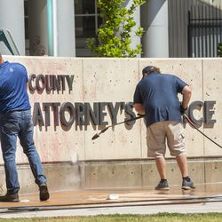 Jason Dixon, sales manager at Royce Industries, and Chad Rasmussen, owner of Royce Industries, clean paint from the sign in front of the Salt Lake County District Attorney's Office building in Salt Lake City on Friday, July 10, 2020. The building suffered tens of thousands of dollars in damage when protesters broke out at least three windows and spread red paint over large portions of the building and area in front of the structure on Thursday.