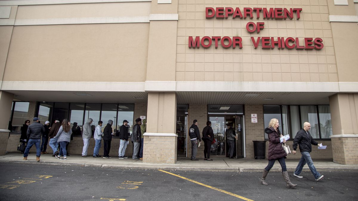 People line up waiting outside of the New York State Department of Motor Vehicles office in Medford, New York.