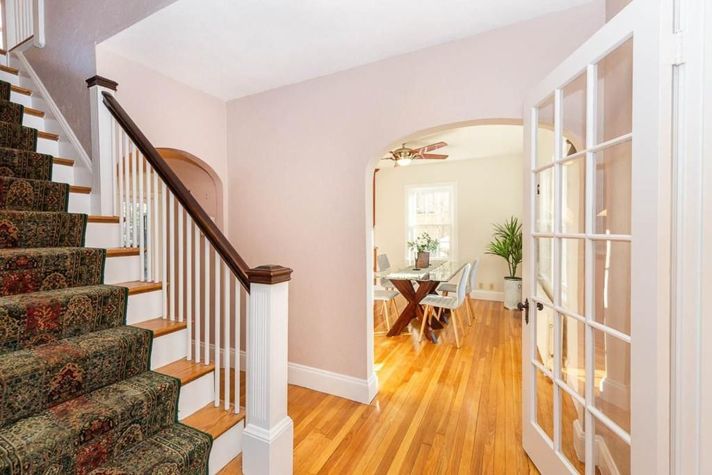 The small entry area of a house with a French door open toward a room and a staircase leading up from the entry area.