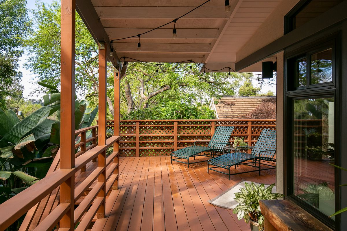 Two deck chairs positioned on a large wooden deck overlooking trees