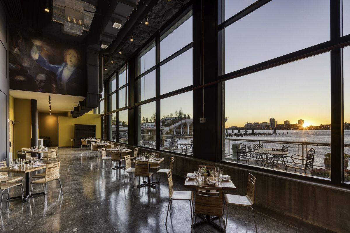 Inside a massive restaurant with chairs and tables placed against a window overlooking a river