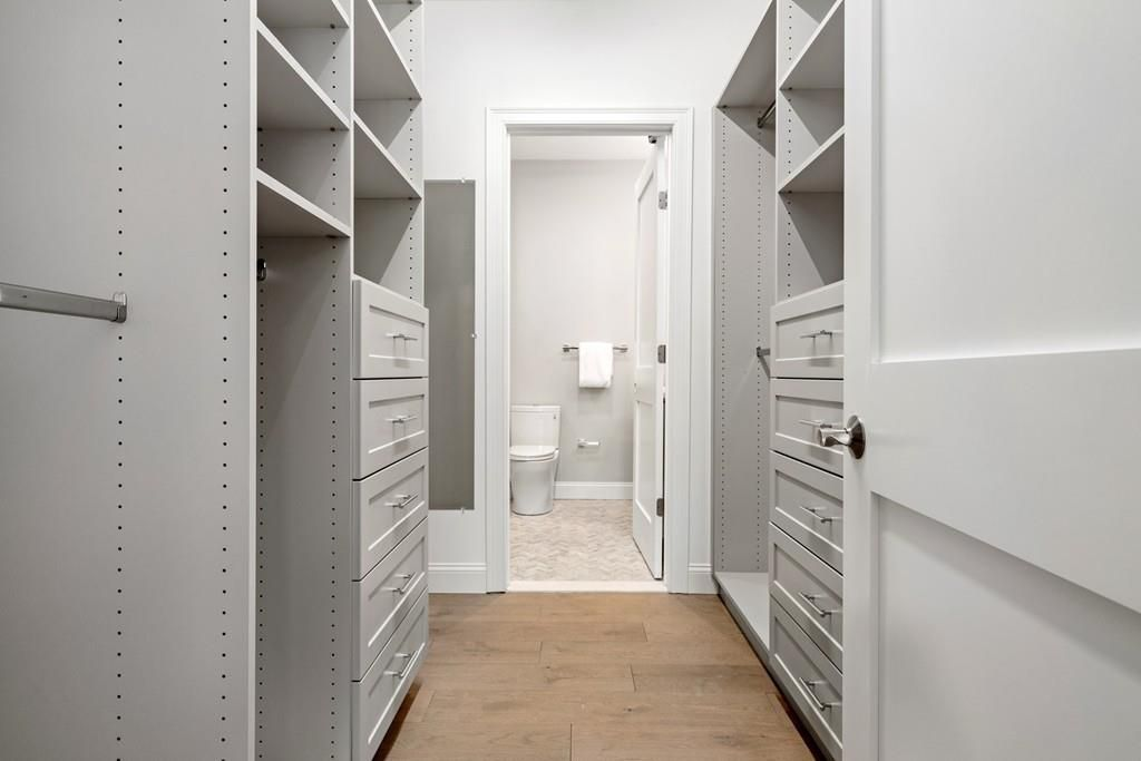 A long, walk-in closet that ends in a bathroom.
