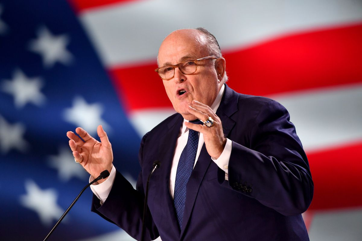 Rudy Giuliani speaking and gesturing from a podium in front of a large US flag.