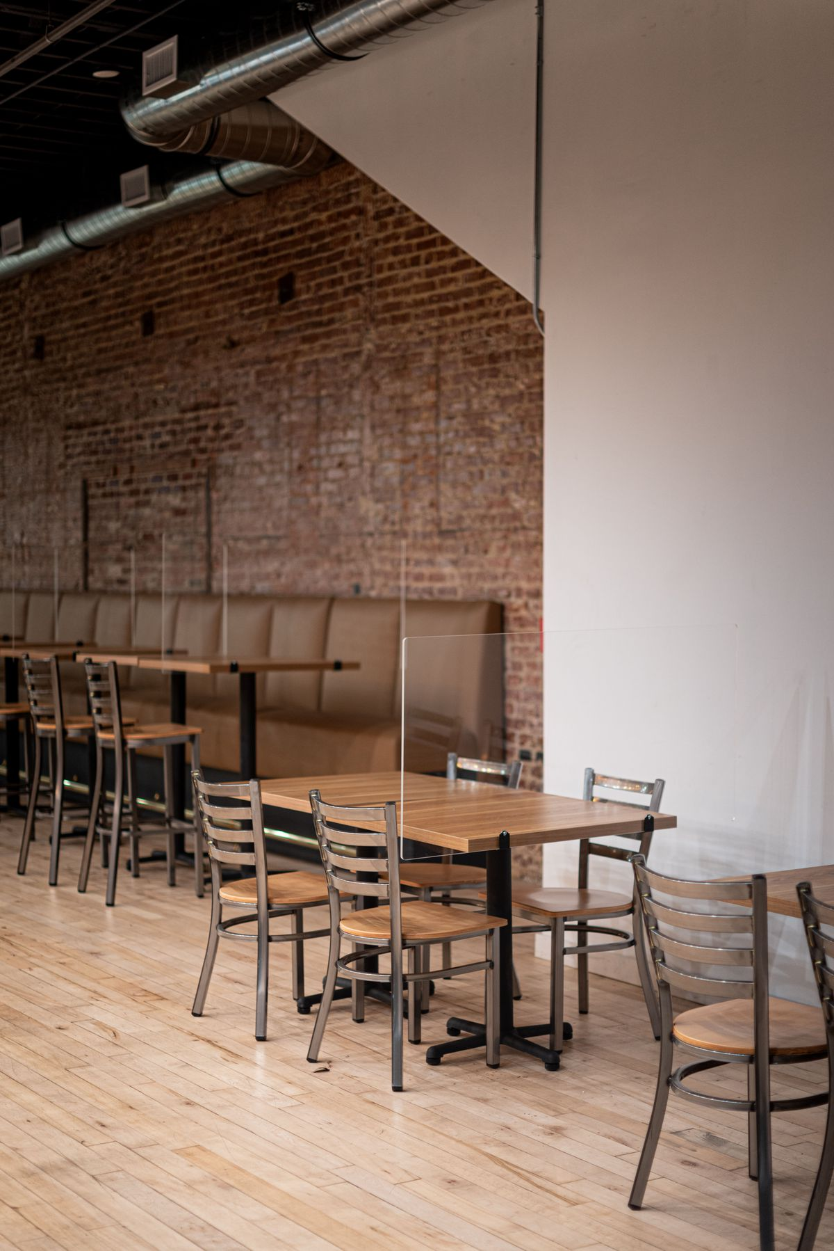Individual tables inside of a restaurant with new glass between, per COVID protocols.