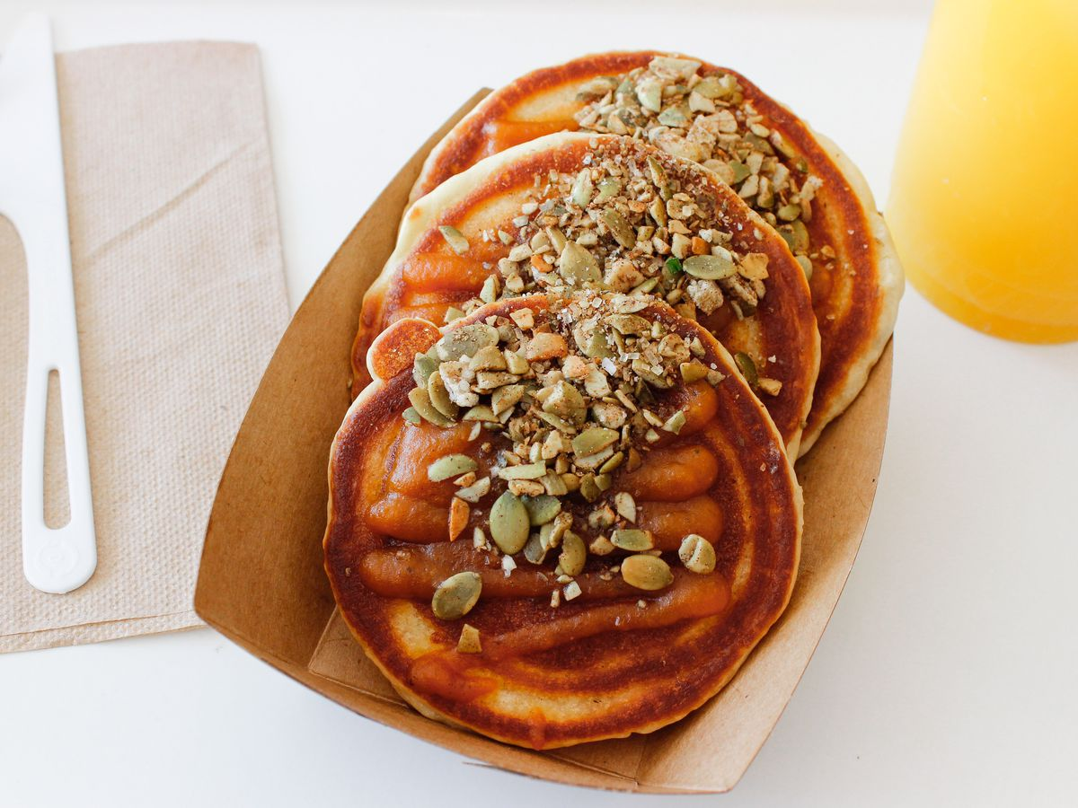 A stack of three pancakes in a paper container, topped with pumpkin seeds. A glass of orange juice is visible on the side.