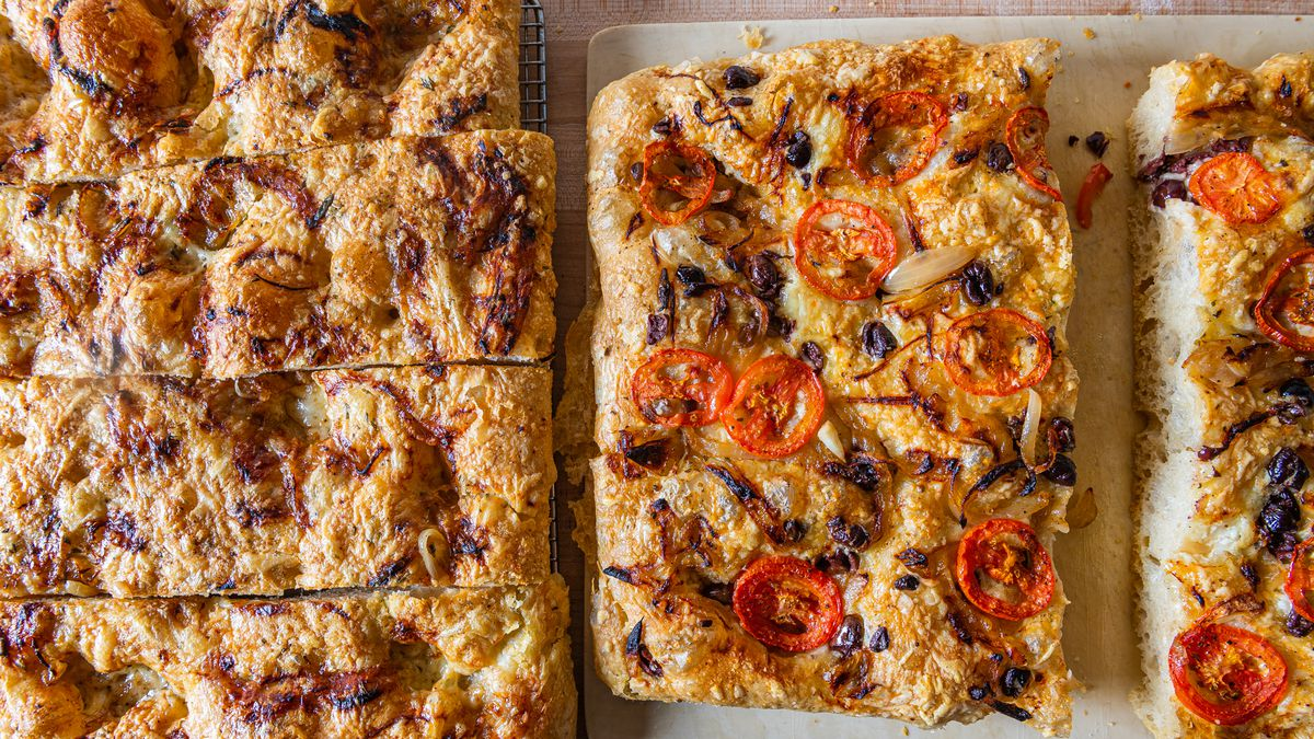 Two sheets of focaccia from Piccolina, covered in tomatoes and onions, respectively