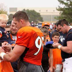 Denver Broncos DE Derek Wolfe (left) and DT Mitch Unrein sign autographs after day 5 of training camp