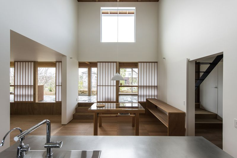 An open dining room with tall ceilings, wooden sideboard and table, and steps out to a stone terrace.