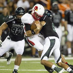 Lamar quarterback Ryan Mossakowski, center, gets sacked by Hawaii defensive back Bubba Poueu-Luna, right,  and defensive lineman Beau Yap, left, during the second quarter of the NCAA game between the Lamar and Hawaii, Sept. 15, 2012 in Honolulu.