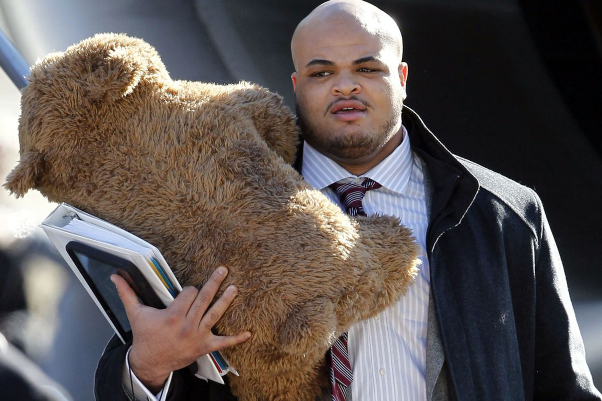 New York Giants tackle James Brewer carries a stuffed bear as the Giants arrived for Super Bowl XLVI in Indianapolis.