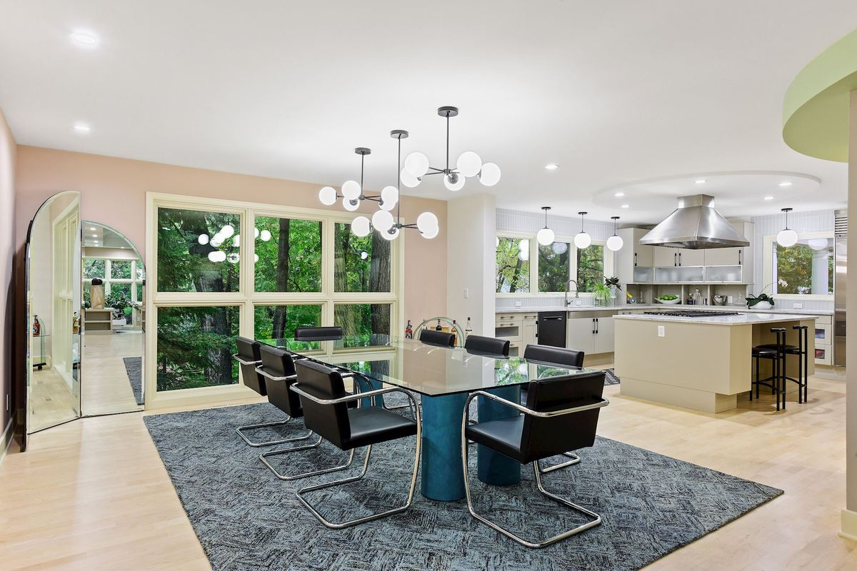 A glass dining room table with black chairs sits under a pendant chandelier and a gray rug. The kitchen is in the background.