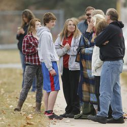 Parents wait for their children as Fremont High School students are evacuated from the school after reports of a student with a gun were made in Ogden Monday, Dec. 1, 2014.