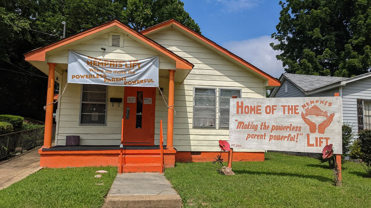 """An orange and white home sits in a North Memphis neighborhood with a sign in front of it that says, """"Home of The Memphis Lift: Making the powerless parent powerful!"""""""