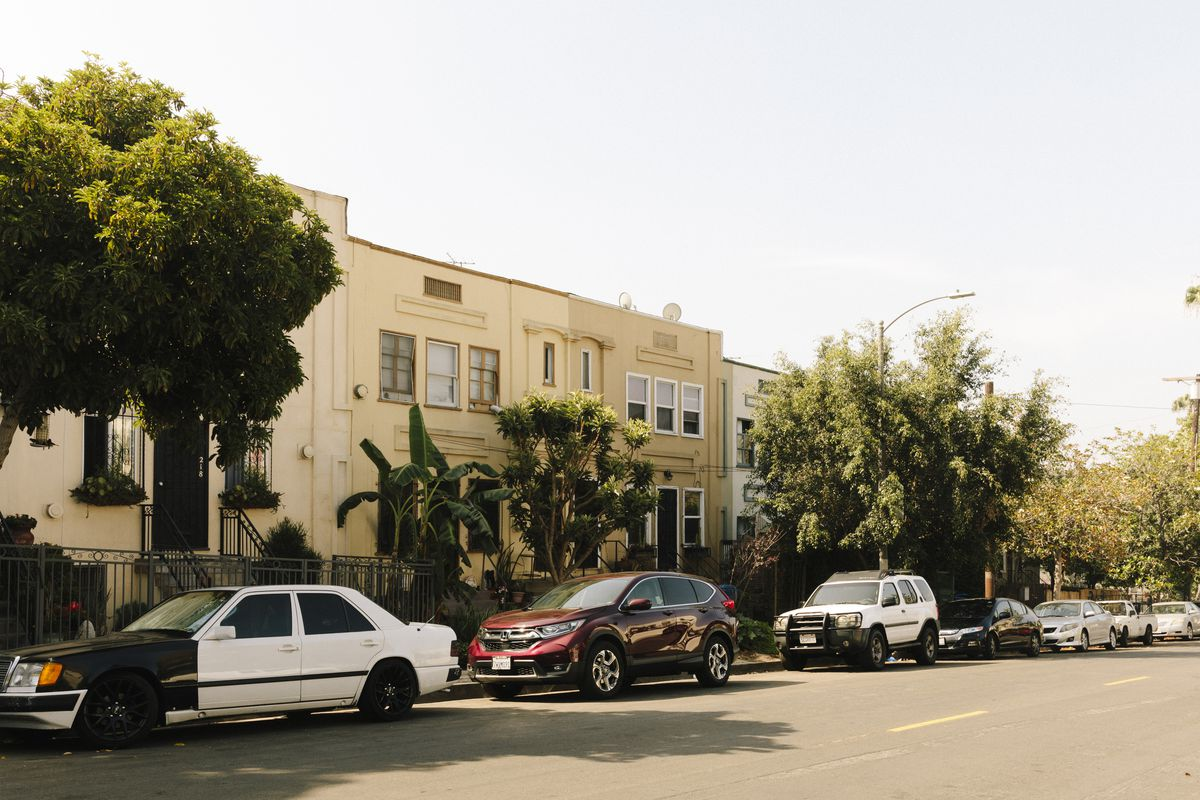 A row of low-rise apartments on a street with a few trees and cars parked at the curb.