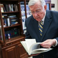 """Elder M. Russell Ballard, of the Quorum of the Twelve Apostles of The Church of Jesus Christ of Latter-day Saints, flips through a copy of the book """"Crusader for Righteousness"""" by his grandfather, Melvin J. Ballard, while speaking to reporters from the LDS Church News in his office at the Church Administration Building in Salt Lake City on Friday, June 30, 2017."""