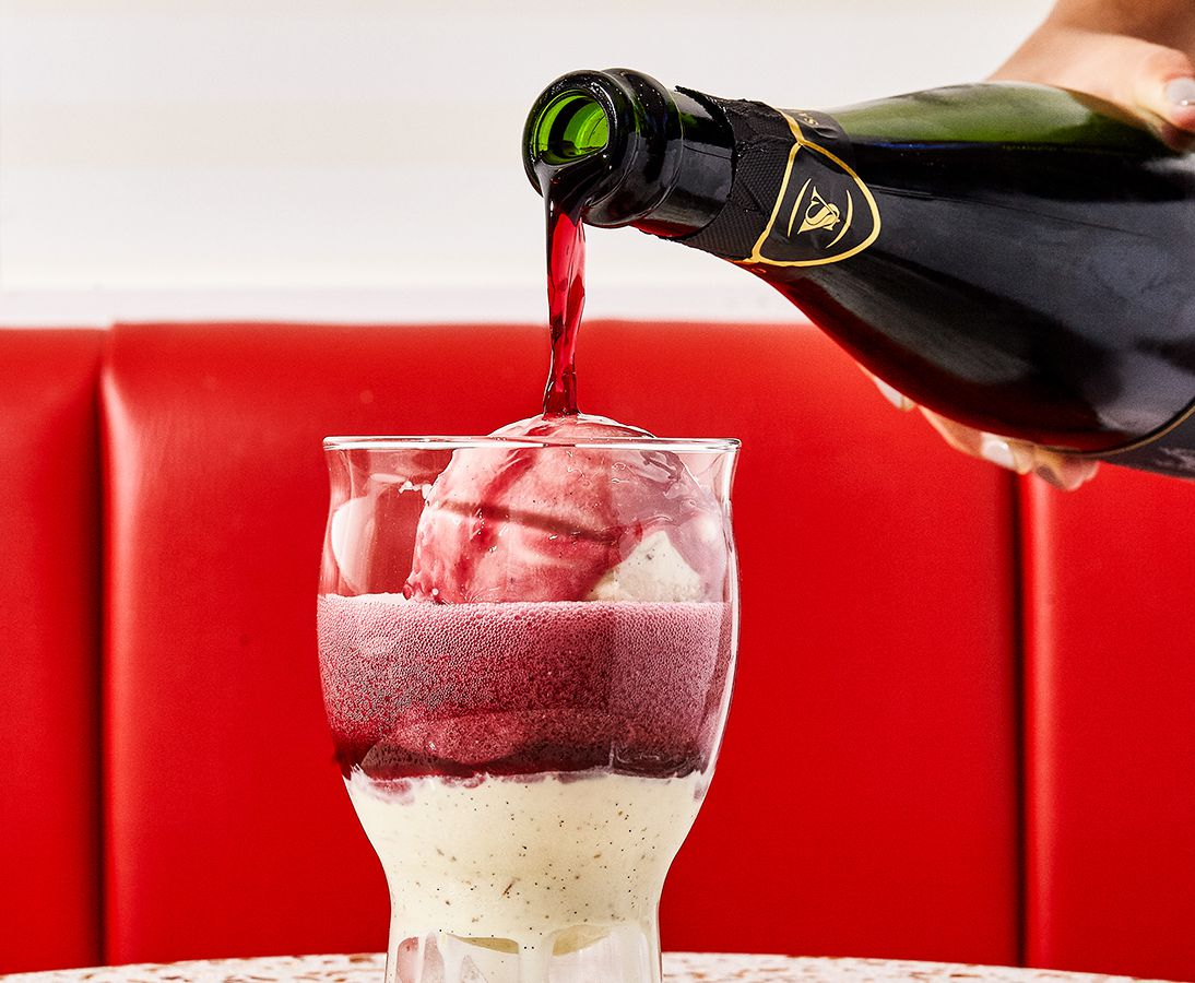A bulbous glass with a scoop of ice cream inside has red wine poured onto it