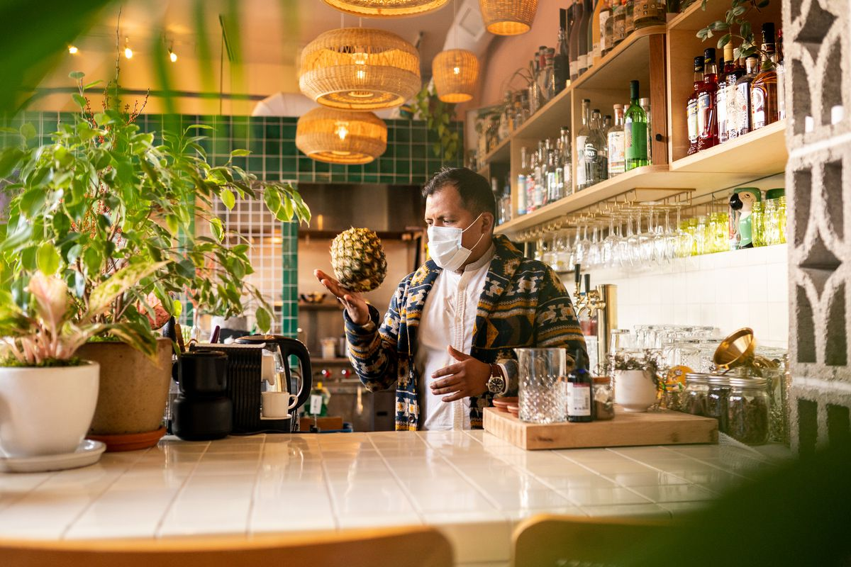 A man lightly bounces a hollowed-out pineapple in his hand in the bar at Tropicale