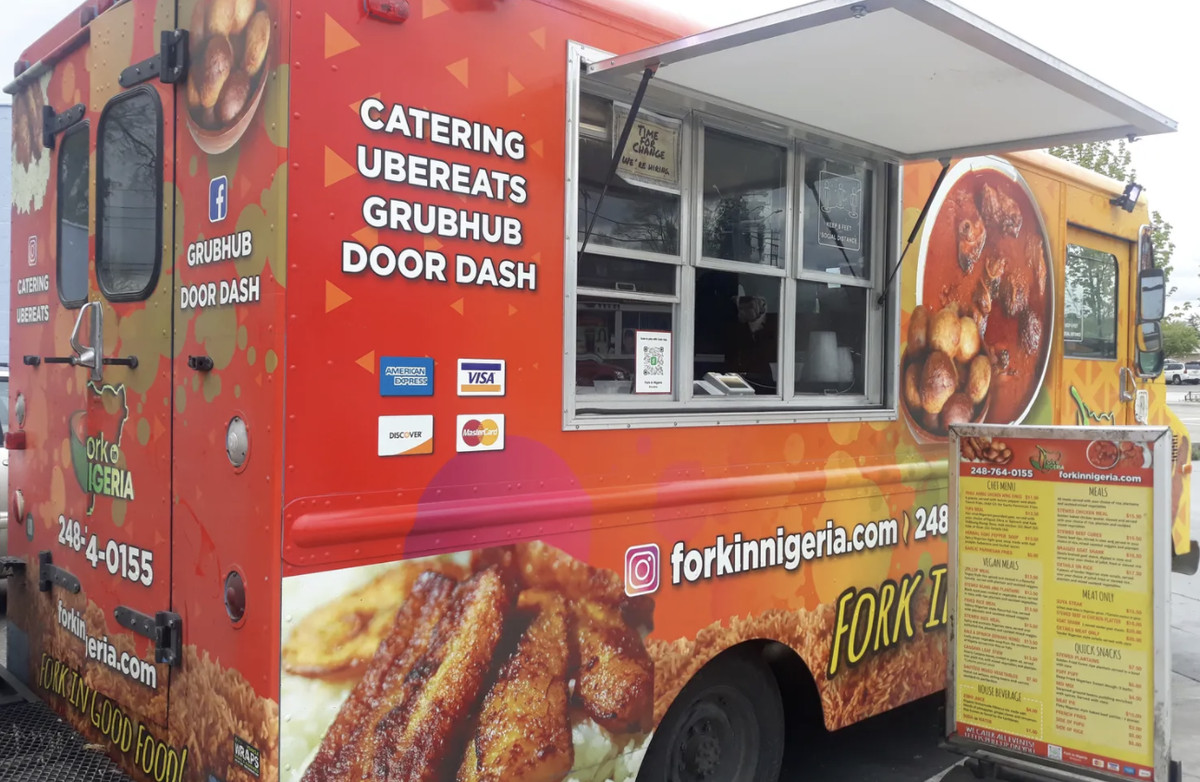 """The side of the Fork in Nigeria food truck shows an open window. Signs on the truck read """"catering,"""" Ubereats, Grubhub, and indicate it accepts credit cards"""