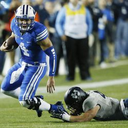 Brigham Young Cougars quarterback Taysom Hill (4) is shoe string tackled by Utah State Aggies linebacker Nick Vigil (41) in Provo Friday, Oct. 3, 2014.